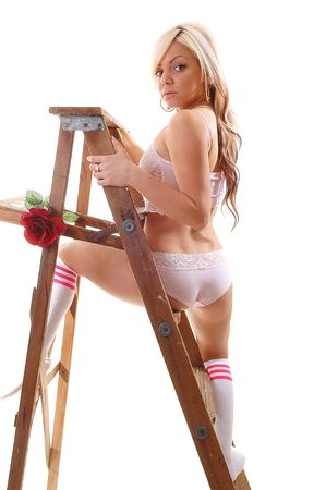 long socks: Pretty young girl in pink underwear and gray socks with long blond hair standing on the wooden stepladder, holding an red rose in her mouth.