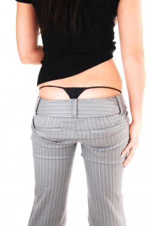 hot ass: The back of an young woman in a gray dress pants and black sweater shooing her black thong underwear, for white background.