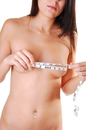 Pretty slim young woman with long brown hair measuring her breasts and shooing her nice body and stomach. On white background. Stock Photo - 5219127
