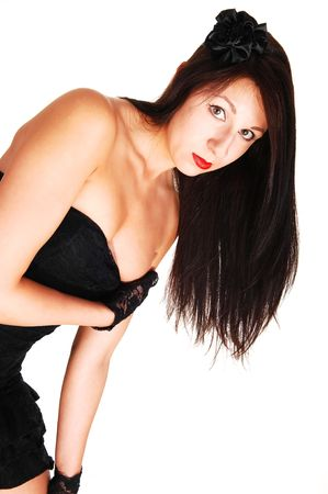 Young black haired woman in an black dress standing in the studio for white background, has her right hand under her bust and leaning forward. Stock Photo - 5248607