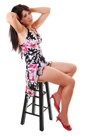 nice legs: Lovely young woman in high heels sitting on a chair in the studio with long  brown hair, shooing her nice legs. On white background.
