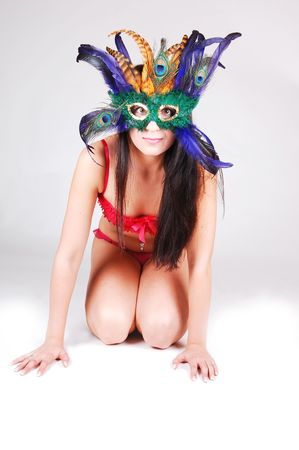 A pretty young girl in red lingerie and a feather mask on her face kneeling on the white floor, what turns light gray in the back. photo