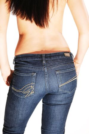 Young topless woman standing with her back to the camera, shooing the nice butt in the blue jeans and the hands in the pocket, over white. photo