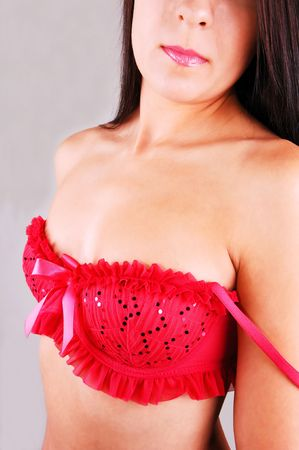 Young pretty woman with an very nice red bra, the shoulder strap are down, for light gray background. Stock Photo - 5312680