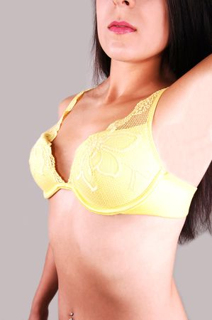 A pretty young woman standing in the studio wearing only a very nice yellow bra and lifting her left arm, for light gray background. Stock Photo - 5312694