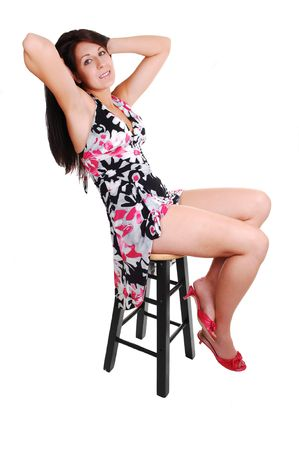 Lovely young woman in high heels sitting on a chair in the studio with long  brown hair, shooing her nice legs. On white background.