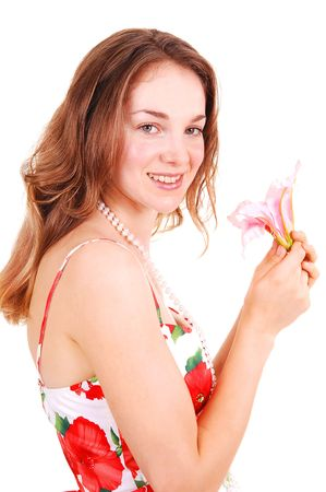 A very pretty young girl in an red rose dress and gorgeous long red hair standing und holding a pink Lilly to her face, on white background. photo