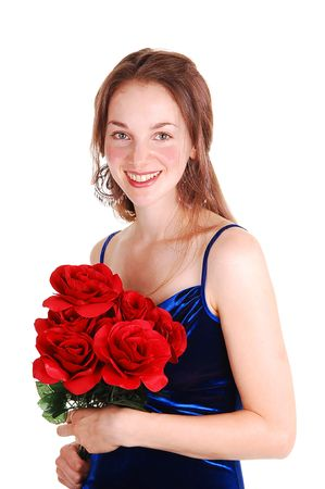velvet dress: Pretty young woman standing in the studio in an royal blue velvet dress, holding a bunch of red rose in her hand. For white background.