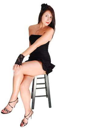 Young lovely girl in a short black dress with red lips and high heels sitting in the studio for white background. Stock Photo