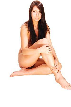 Mujer desnuda con el pelo casta�o y largo sentado en el suelo, mostrando sus brazos alrededor de las piernas, sonriendo a la c�mara, sobre fondo blanco. Foto de archivo - 5439004