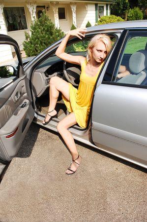 gambe aperte: Una giovane ragazza in un vestito giallo e lunghe gambe seduto in macchina con una porta aperta, nel vialetto di casa sua paese bello, bellissimo sole.