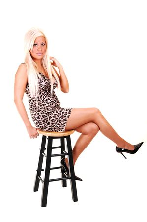Young, lovely girl in a brown and white dress sitting on a green bar chair in high heels with her long blond hair, in the studio for white background. Stock Photo - 5526160