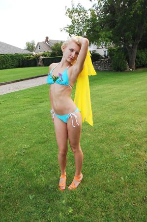 An slim young girl in a turquoise bikini and an yellow scarf in her hand  dancing on the grass in the backyard by the beach.  photo