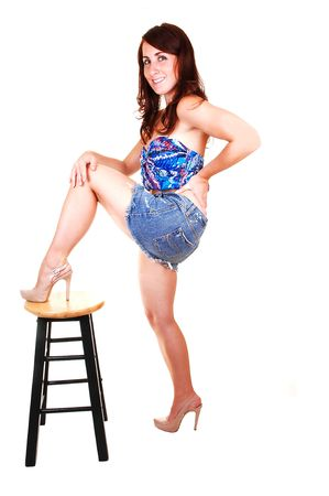 A lovely young girl in an jeans mini skirt and blue blouse with her red hair falling over her shoulder and one leg on the bar chair, over white. photo
