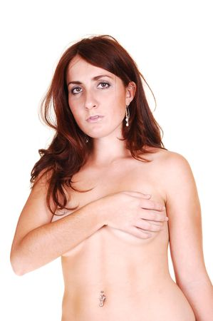 A young topples woman with long red hair standing in the studio and  covering her breasts up with one hand and arm, for white background. photo