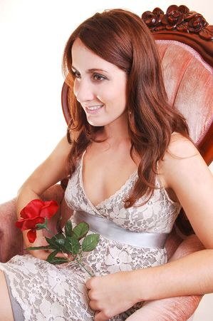 A very pretty young girl in an gray, white dress and gorgeous long red hair sitting in a pink armchair, holding a red rose in her hand, on white background. photo