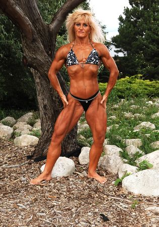 An blond bodybuilding woman standing on some rocks in front of trees in a park, shooing her good trained and lean body.  Archivio Fotografico