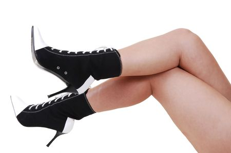 The nice legs of a young woman, lying on the floor, with high heel boots in black and white. Stock Photo - 5630191