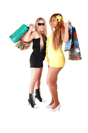 One Asian and one Caucasian woman standing together are back from a shopping trip and shooing there nice legs and bum, on white background. photo