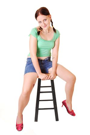 Young, lovely girl in a green top and jeans shorts and red high heels sitting in the studio with her nice pigtails, for white background. Stock Photo - 5646312
