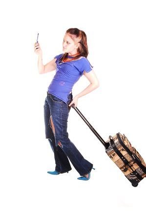A pretty young girl with an suitcase and torn up jeans on a trip, holding up her cell phone to get the message, on white background. Stock Photo - 5646317