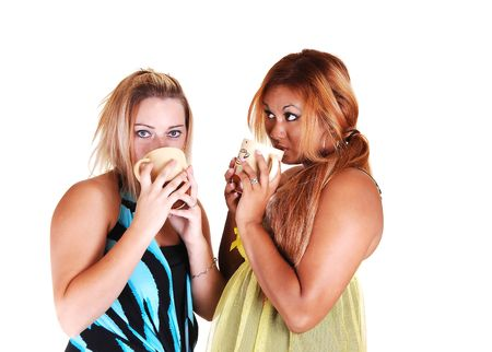 One Asian and one Caucasian woman standing together holding a cup of and having a nice shat together, on white background. photo