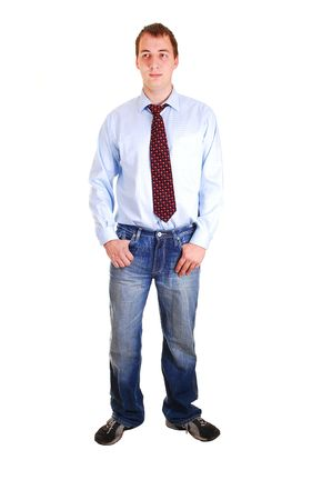A young teenager in jeans and blue dress shirt with tie standing in the studio for white background isolated. Stock Photo