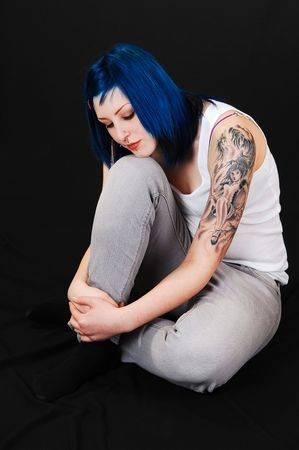 Young lovely girl in gray blue jeans and white T-Shirt, sitting on the floor and  dreaming, with a nice tattoo on her arm, for black background. photo