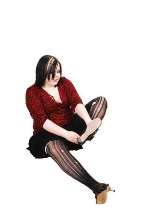 A young girl in a black short skirt and red blouse sitting on the floor and putting her high heels on in ripped up pantyhose, on white background. photo