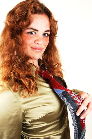 hair tie: An close up of a pretty red haired girl in a gold blouse and necktie, smiling in the camera, on white background. Stock Photo