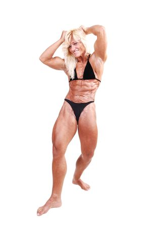 A strong blond woman in an black bikini, standing bare foot in the studio and shooing her muscular body and bicep, over white background. Imagens