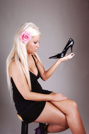 Young, lovely girl in a short black dress with long blond hair, sitting on a  bar chair and holding her high black heel, on white background photo
