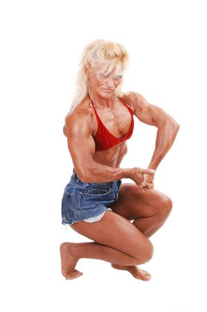A blond muscular bodybuilding girl kneeling in the studio, shooing her  strong legs and the upper body and arms, over white background.