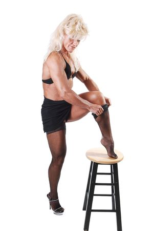 A blond wery muscular bodybuilding woman putting on her black stockings in the studio, for white background. photo