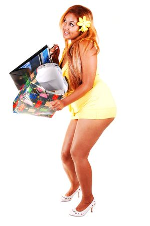 A pretty red haired girl in a short yellow dress, with shopping backs in her hand, smiling as she sees the backs are empty, for white background. photo