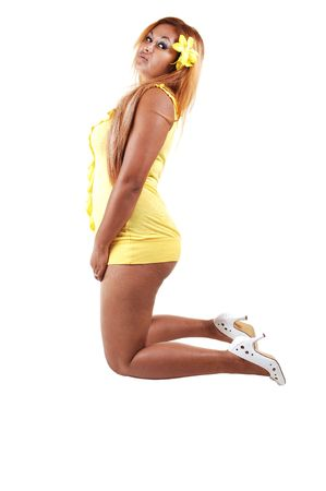 An young Asian girl in a short yellow dress and high heels kneeling  on the floor and shooing her nice legs, on white background. photo