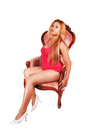 A pretty girl with long red hair sitting in an pink armchair in a bright red dress and white high heels shooing her nice legs, for white background. photo