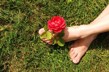 The feet of a young woman, sitting on the grass with a red rose between  her toes.