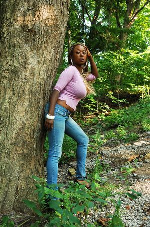 An Jamaican woman in jeans and pink sweater leaning on a big tree in the woods, in nice sunshine. photo