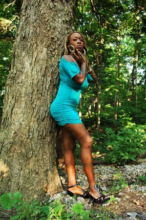 An Jamaican woman in a short turquoise dress leaning on a big tree in the forest, shooing her nice figure and long hair. photo