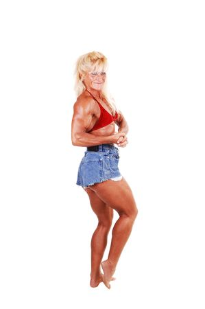 A blond muscular bodybuilding girl standing in the studio shooing her  strong legs and the upper body and arms, over white background.