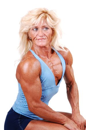 A blond muscular bodybuilding girl sitting in the studio shooing her  strong legs and the upper body, over white background. photo