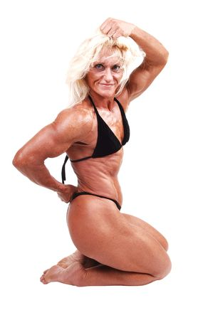 A blond muscular bodybuilding girl kneeling in the studio shooing her  strong legs and the upper body and arms, over white background.