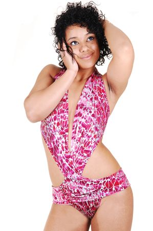 An pretty young woman with a nice slim body, with curly black hair standing in a studio for white background. photo