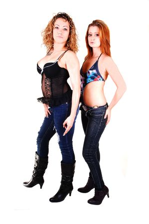 Two young woman in bikini and jeans with black boots standing in a studio for white background photo