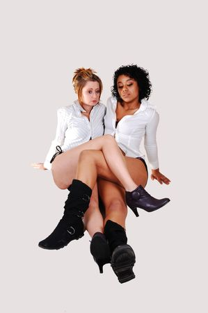 Two young woman in bikini and white blouse and black boots sitting on the floor crossing there legs, in a studio for white background photo