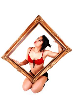 A lovely young Hispanic woman kneeling in the studio in a red bra and black panties, holding a gold picture frame for white background. photo