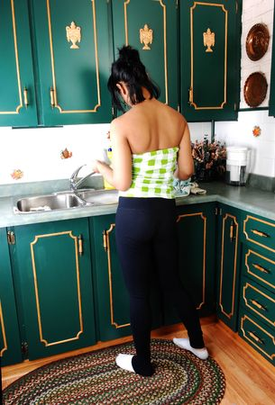 A young pretty Hispanic woman washing dishes in the kitchen with green cupboards, wearing just a black shorts and red bra. Stock Photo - 6314960