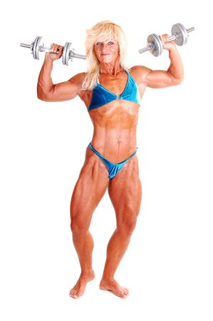 A blond muscular bodybuilding girl standing in the studio shooing her strong legs and the upper body and arms, with dumbbells, over white background. photo
