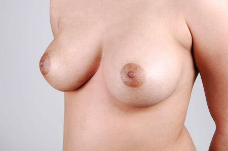 A closeup shoot of the beautiful breasts of a young woman, for light gray background.
